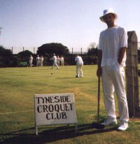 Photo of John Moore in croquet whites and floppy sunhat standing beside a Tyneside Croquet Club sign.