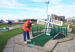 Photo of John Moore playing a shot at the crazy golf hole with the windmill.