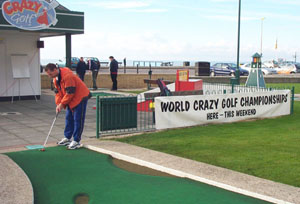 Photo of John Moore on first hole at Hastings Crazy Golf. Banner advertising the World Championship is displayed nearby.