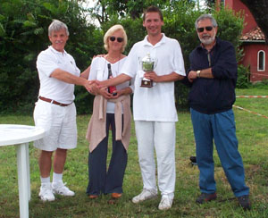 Photo of four people at the presentation for the Italian Open, with John Moore holding the trophy.