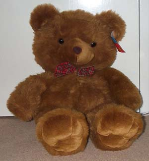 Photo of a large brown teddy bear wearing a bow tie, sitting on the floor propped up against a door.
